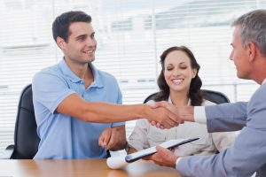 Handsome Man With His Wife Shaking Hands With Estate Agent In Bright Office